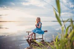 Menina bonito da criança que senta-se em uma plataforma de madeira pelo lago Fotografia de Stock