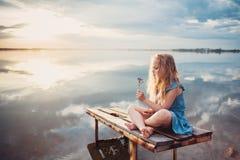 Menina bonito da criança que senta-se em uma plataforma de madeira pelo lago Fotos de Stock
