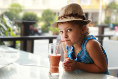 Menina bonito da criança do divertimento curioso que bebe o suco saboroso na rua do verão Fotografia de Stock Royalty Free