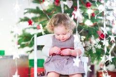Menina bonito da criança que come doces sob a árvore de Natal Fotos de Stock Royalty Free