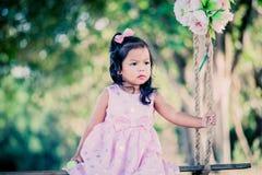 Menina bonito da criança que senta-se no balanço no parque Fotografia de Stock Royalty Free