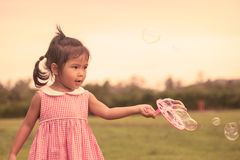 A menina bonito da criança que tem o divertimento a jogar com suas bolhas brinca Fotografia de Stock