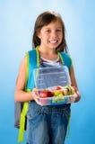 A menina bonito da escola mostra sua lancheira saudável fotos de stock royalty free