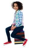 Menina bonito da escola que senta-se na pilha de livros Fotografia de Stock