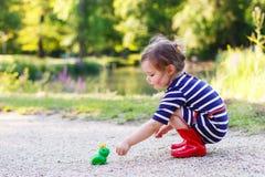 Menina bonito da princesa nas botas de chuva vermelhas que jogam com o brinquedo de borracha para Foto de Stock