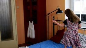 A menina bonito dança em uma cama Movimento lento Conceito da infância vídeos de arquivo