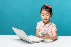 A menina bonito de Ásia está sentando-se na tabela com seu portátil branco Foto de Stock