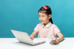 A menina bonito de Ásia está sentando-se na tabela com seu portátil branco Imagens de Stock Royalty Free