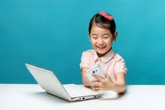 A menina bonito de Ásia está sentando-se na tabela com seu portátil branco Fotos de Stock Royalty Free