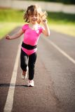 Menina bonito de Ittle que corre no estádio Imagens de Stock Royalty Free