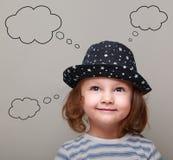 Menina bonito de pensamento da criança com muitas ideias Foto de Stock Royalty Free
