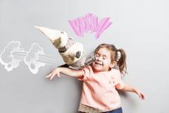 Menina bonito de riso pequena que luta com gato do brinquedo Cena cómica Imagem de Stock Royalty Free