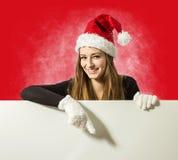 Menina bonito de Santa que apresenta algo na placa de escrita branca fotografia de stock royalty free