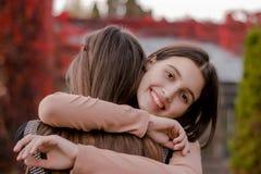 A menina bonito de sorriso abraça sua amiga firmemente imagens de stock royalty free