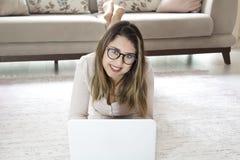Menina bonito de sorriso bonita que encontra-se no assoalho e que usa o portátil fotografia de stock royalty free