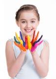 Menina bonito de sorriso com mãos pintadas. Imagem de Stock