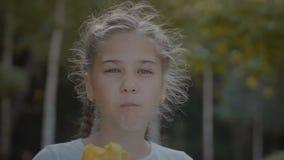 Menina bonito de sorriso do preteen que come o pêssego fora vídeos de arquivo
