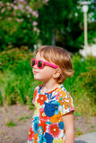 Menina bonito de sorriso em óculos de sol cor-de-rosa Imagens de Stock Royalty Free