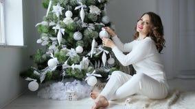 A menina bonito decora a árvore de Natal festiva em tons brancos macios na atmosfera da celebração vídeos de arquivo
