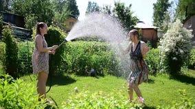 A menina bonito derrama sua água da amiga da mangueira de jardim no gramado verde em um dia ensolarado do verão quente Louro e mo video estoque