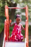 Menina bonito do americano africano no campo de jogos Imagem de Stock