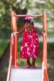 Menina bonito do americano africano no campo de jogos Fotos de Stock Royalty Free
