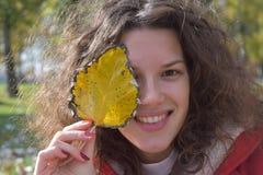 Menina bonito do outono com folha amarela Fotos de Stock Royalty Free