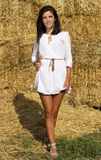 A menina bonito do país perto de uma palha empacota a parede Imagens de Stock Royalty Free