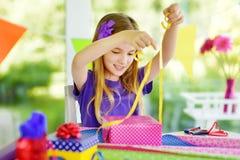Menina bonito do preteen que envolve presentes no papel de envolvimento colorido Imagens de Stock Royalty Free