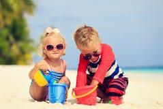 A menina bonito do rapaz pequeno e da criança joga com a areia na praia Imagens de Stock Royalty Free