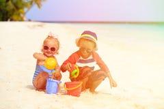 A menina bonito do rapaz pequeno e da criança joga com a areia na praia Imagens de Stock