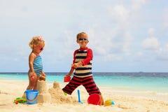 A menina bonito do rapaz pequeno e da criança joga com a areia na praia Fotos de Stock Royalty Free