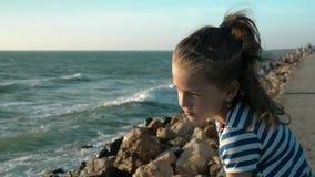 Menina bonito do retrato em t-shirt listrado no dia ventoso da praia no por do sol Concentração do pensamento do conceito video estoque