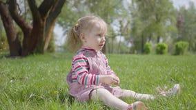 Menina bonito do retrato que senta-se na grama no parque, jogando apenas, apontando com um dedo minúsculo acima carefree filme