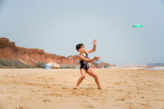 Menina bonito do youg no roupa de banho que está em uma praia pelo mar que joga um disco verde Imagem de Stock Royalty Free