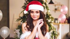 A menina bonito doce em um tampão de ano novo de um traje do Natal no fundo da árvore e dos balões de Natal envia video estoque