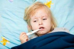 A menina bonito doente está medindo a temperatura Fotografia de Stock