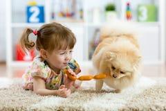 Menina bonito e cão engraçado em casa fotografia de stock royalty free