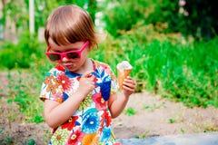 Menina bonito e feliz nos óculos de sol cor-de-rosa que sentam e que comem o gelado exterior Fotografia de Stock