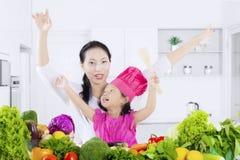 Menina bonito e mãe com vegetais fotografia de stock royalty free
