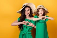 Menina bonito e mãe que guardam as mãos na forma do coração no fundo branco Fotos de Stock