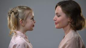 Menina bonito e mãe que tocam nas testas, amizade fêmea, apoio da família filme