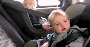 Menina bonito e menino que sentam-se no banco traseiro do carro video estoque