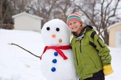Menina bonito e seu boneco de neve Imagens de Stock