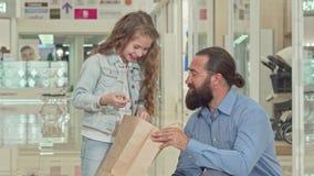 Menina bonito e seu pai que olham sacos de compras internos na alameda video estoque
