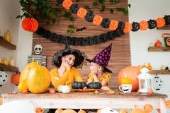 A menina bonito e sua mãe, ambos os chapéus vestindo da bruxa, sentando-se atrás de uma tabela no tema de Dia das Bruxas decorara fotos de stock