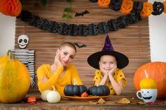 A menina bonito e sua mãe, uma paciente que sofre de câncer, sentando-se atrás de uma tabela no tema de Dia das Bruxas decoraram  fotografia de stock royalty free