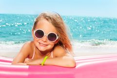 Menina bonito em óculos de sol redondos que toma sol na praia Foto de Stock Royalty Free
