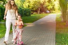 A menina bonito em pouco 'trotinette' cor-de-rosa tem o divertimento com a mãe na paridade Foto de Stock Royalty Free