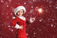 Menina bonito em sparklers da terra arrendada do chapéu de Santa Fotografia de Stock